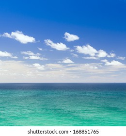 Bright blue sea beneath the blue sky with clouds