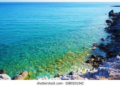 Bright blue sea and stony shore