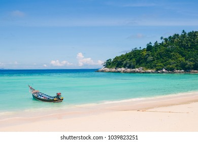 Bright blue sea and white sandy beach on summer sunny day with traditional Thai boat. Tropical beach and blue ocean as background.
