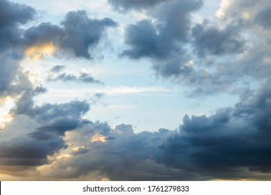 Bright blue sky is visible through the gap in the dark clouds at evening. Rain clouds surround the last spot of a clear sky. Rift in the clouds. Scenic skyscape.