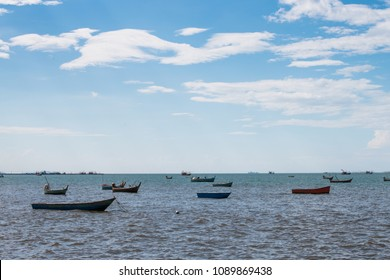 Bright blue sky with vivid clouds and boats scattered in the ocean