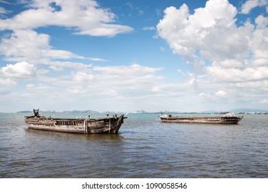 Bright blue sky with the wreckage of two wooden boats and some herons