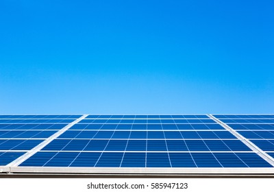 Bright blue solar panels on blue clear sky background in sunny weather