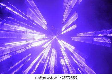 Bright blue spotlight or strobe sending vibrant colorful beams of light through the darkness at a concert or disco party