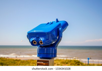 Bright blue tourist pay binoculars at seaside