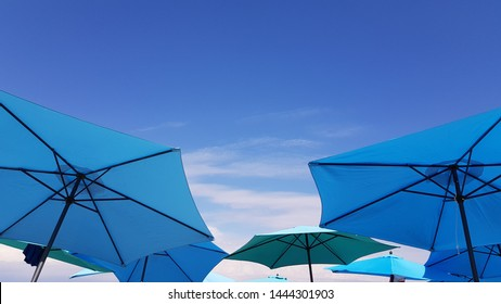 Bright blue and turquoise color parasols on blue sky backgrounds with light white spindrift clouds. Geometry of beach umbrellas. Sea vacation backdrop. Sunshades at seaside. Summer sunny weather.