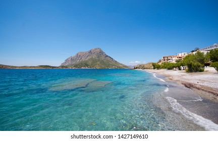bright blue turquoise sea and pebbles beach with hills Telendos's Island at the background in Greece Island Kalymnos