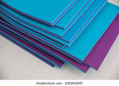 Bright blue and violet yoga fitness mats lying on a floor in a sport gym. Fitness equipment details.