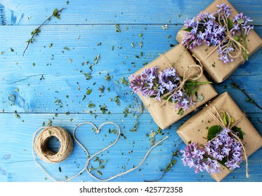 Bright blue wooden background with small gift boxes wrapped with simple brown paper and decorated with natural lilac. Floral decor elements. Copy space