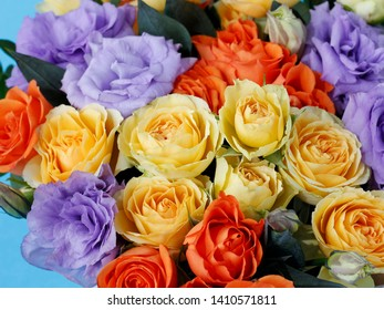 bright bouquet of flowers: orange roses, yellow roses, delicate purple eustoma close-up on a blue background with a blurred background