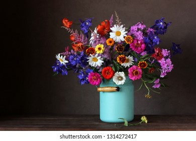 bright bouquet of garden cultivated flowers in a can on the table. place Your text on the left.