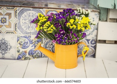 Bright bouquet of summer flowers in a watering-can on the table