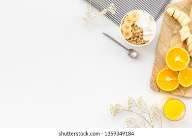 Bright breakfast with granola and orange juice on white background top view mockup