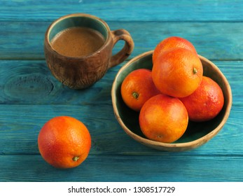 Bright breakfast table with cup of black coffee in a nice mug and red blood oranges