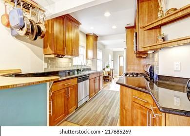 Bright brown kitchen cabinets with black granite tops. Kitchen room with tile back splash trim, hardwood floor and stripped rug