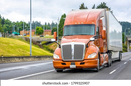 Bright brown professional big rig bonnet long haul diesel semi truck transporting commercial cargo in dry van semi trailer moving on the straight wide highway road with bridge and hill