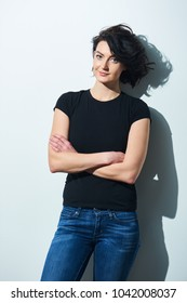Bright brunette woman in black tshirt and jeans standing by the wall with folded hands