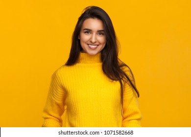 Bright brunette in yellow sweater smiling excitedly at camera standing on yellow background.