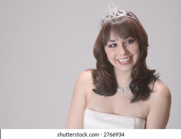 Bright and bubbly young woman just crowned prom or beauty queen, wearing a sparkling tiara