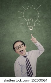 Bright business kid pointing his finger on hand drawn lightbulb