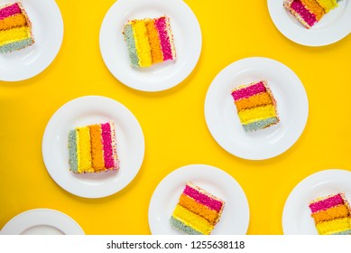 Bright cake pattern. Top view set of rainbow cake slices on white round plates on yellow background. Happy bithday, party layout concept. Selective focus. Copy space