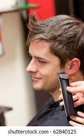 Bright caucasian man being shaved in a hairdressing salon