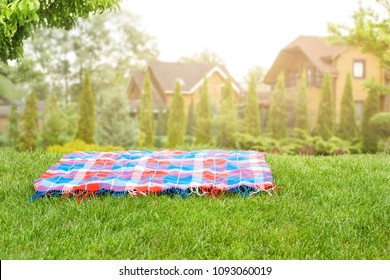 Bright checkered mat on green grass lawn under trees in garden. Blurred wooden houses on background. Empty space for product display. Picnic concept