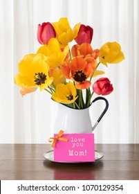 Bright and Cheerful Mothers Day or Birthday Spring Tulip Bouquet in a White Vase on dark wood table and against White Curtain Background with Pink love you Mom Card.  A vertical in natural light