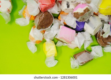 Bright and cheerful saltwater taffy candy in pile against green background with copy space.