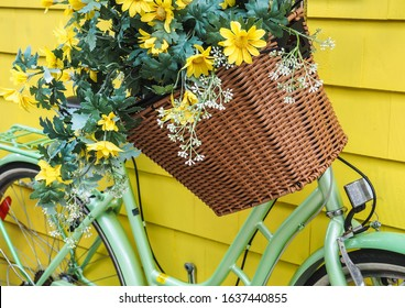 Bright and cheerful spring / summer scene. Wicker bike basket full of artificial yellow flowers on green bicycle with yellow background.