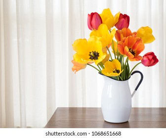 Bright and Cheerful Spring Tulip Bouquet in a White Metal Vase on dark wood and against White Curtain Background with room or space for copy, text, your words or design.  A horizontal in natural light