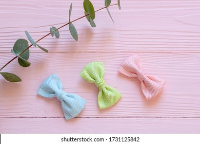 Bright children's hair accessories on a pink wooden background, Children's hair bands in the form of bows