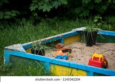 bright children's plastic toys lie on the sand in the sandbox without children in the yard at the playground