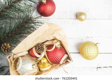 Bright Christmas background with red and gold xmas toys in box on wooden table. Focus on box. New year concept. Text space