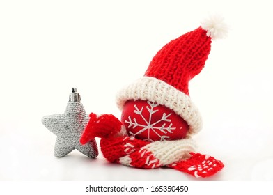 Bright Christmas composition - red Christmas ball with scarf, winter hat and gifts