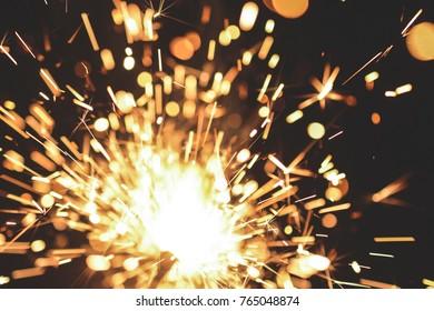 Bright Christmas sparkler closeup on a black background soft focus