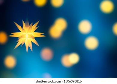 bright christmas star on abstract shiny background, moravian star and bokeh lights on blurred blue sky, xmas decoration with copy space