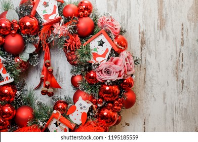 Bright Christmas Wreath decorated with red balls, roses and toy houses on the wooden background