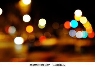 Bright circles from streetlamps on defocused photo of night street.