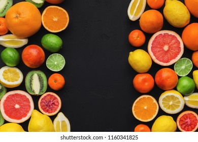 Bright citrus backdrop. Fresh ripe orange, lemon, lime, grapefruit and tangerine fruits on black background, top view, copy space