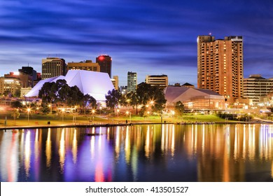 Bright city lights reflecting in still Torrens river waters of Adelaide, capital of South Australia. City architecture illuminated before sunrise.