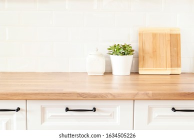 Bright And Clean Kitchen With White Cabinets, Close Up. Cutting Boards, Green Succulent Pot On A Wooden Worktop. Kitchenware In Modern Kitchen Interior. White Tiles Background