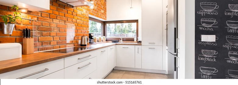 Bright and clean modern minimalist kitchen with white cabinets, brick wall and glass splashback