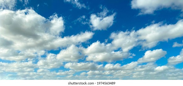 bright clear blue sky and contrasting white cumulous puffy clouds distance perspective