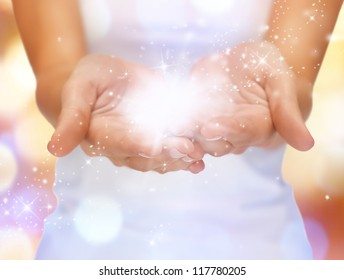 bright closeup picture of magic twinkles on female hands