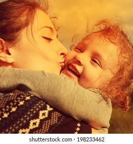 Bright closeup portrait of happy mother kissing laughing daughter. Instagram effect. Happiness of family love.