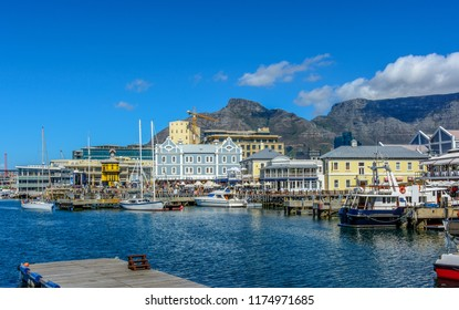 Bright color city and landscape panoramic view of the Table Mountain,Cape Town,South Africa, seen from V&A Waterfront with clock tower,boats in the sea harbor,bright sunny day,blue sky,clouds