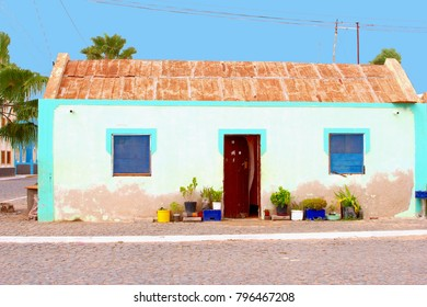 Bright color fisherman house with open door and blue boarded up windows in old street, Cape Verde islands, Africa