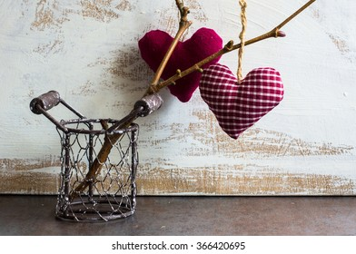Bright color herts on the tree branch in a jar on rustic background for St. Valentines day celebration
