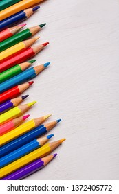 Bright color palette of crayons on the table. 1 September concept postcard, teachers day. Top view, flat lay. copyspace